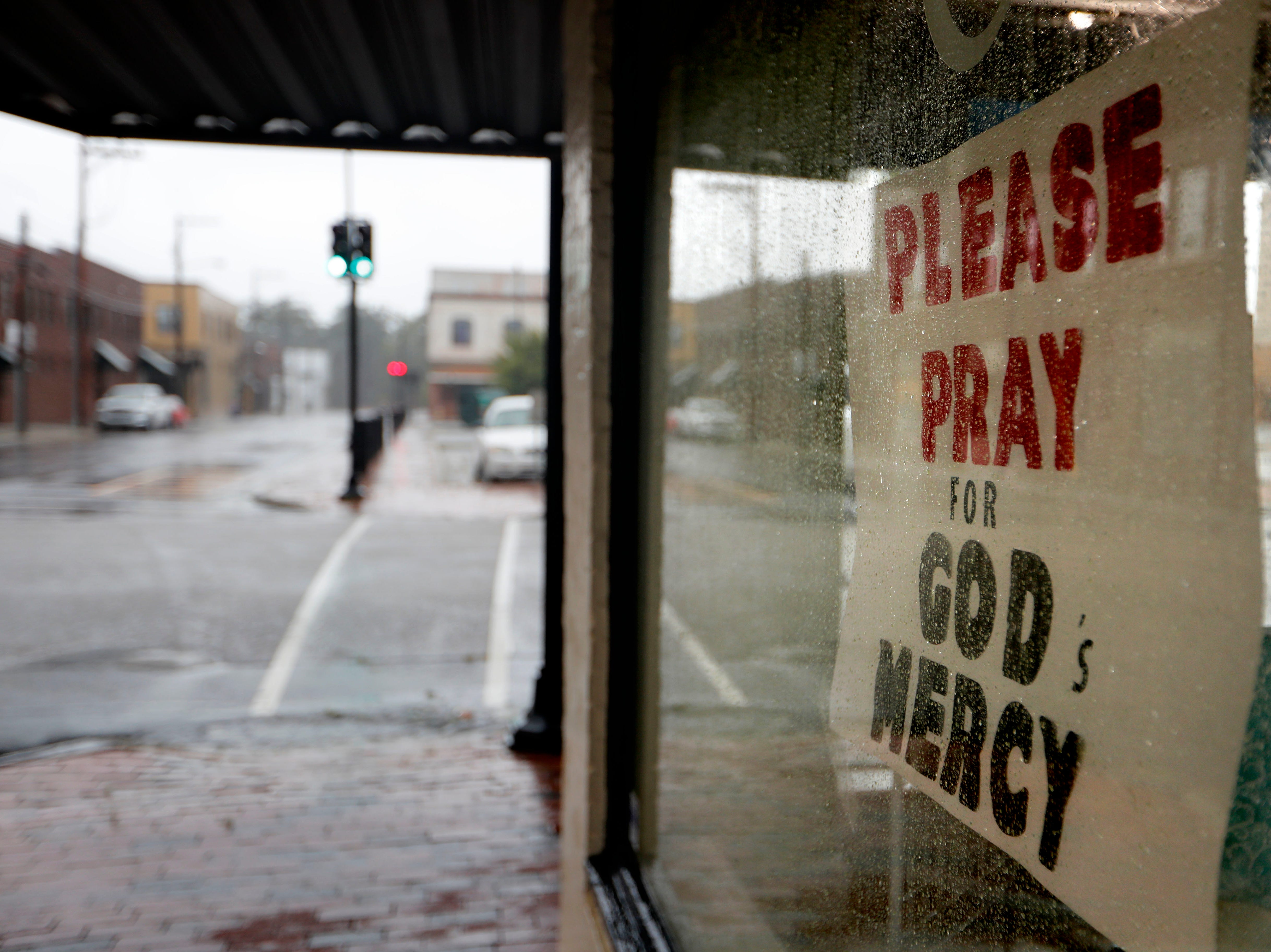 A sign with a message regarding Hurricane Florence hangs in a storefront in Lumberton, N.C., Friday, Sept. 14, 2018. The rural town, battered by the collapse of its blue-collar economy and then by Hurricane Matthew, might also bear the brunt of Florence as the river that cuts through the middle of town continues to rise through the weekend.