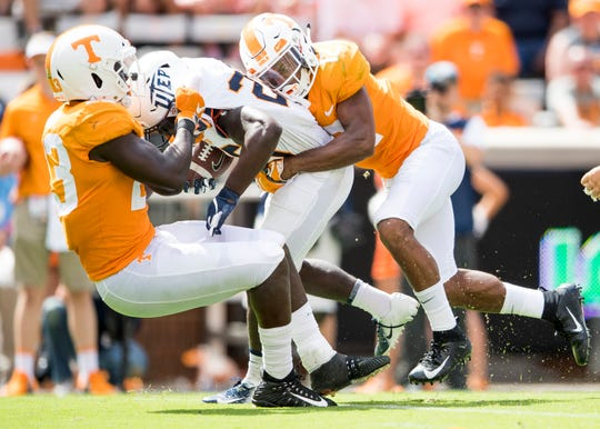Tennessee linebacker Will Ignont (23) and Tennessee defensive back Shawn Shamburger (12) take down UTEP running back Joshua Fields (25) during the Tennessee Volunteers' game against UTEP in Neyland Stadium on Saturday, Sept. 15, 2018.