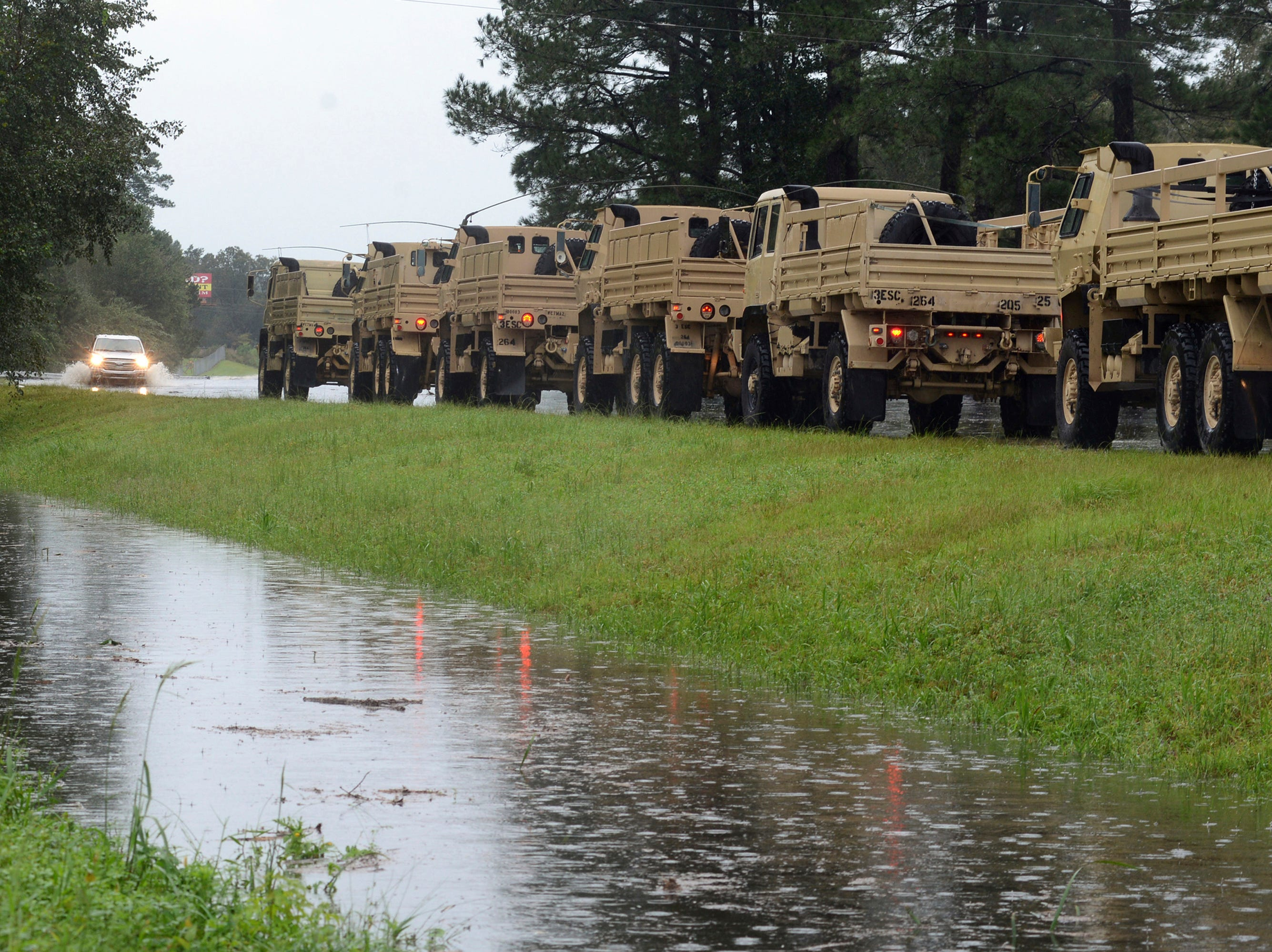 A line of military vehicles waits before driving through floodwaters from Florence rushing across U.S. 70 East near the Lenoir County Shrine Club on Saturday, Sept. 15, 2018 in Kinston, N.C.