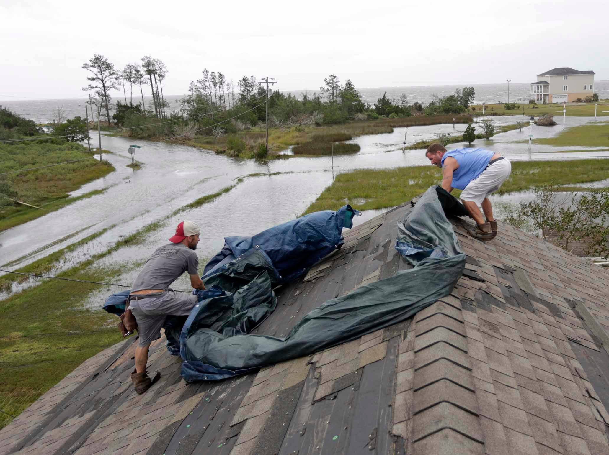 "Jeff Pyron, left, and Daniel Lilly cover Lilly's roof after Hurricane Florence hit Davis N.C.,Saturday, Sept. 15, 2018. Lilly said, ""I had my house raised for Irene cause I got flooded from the bottom, now i'm getting flooded from the top""."