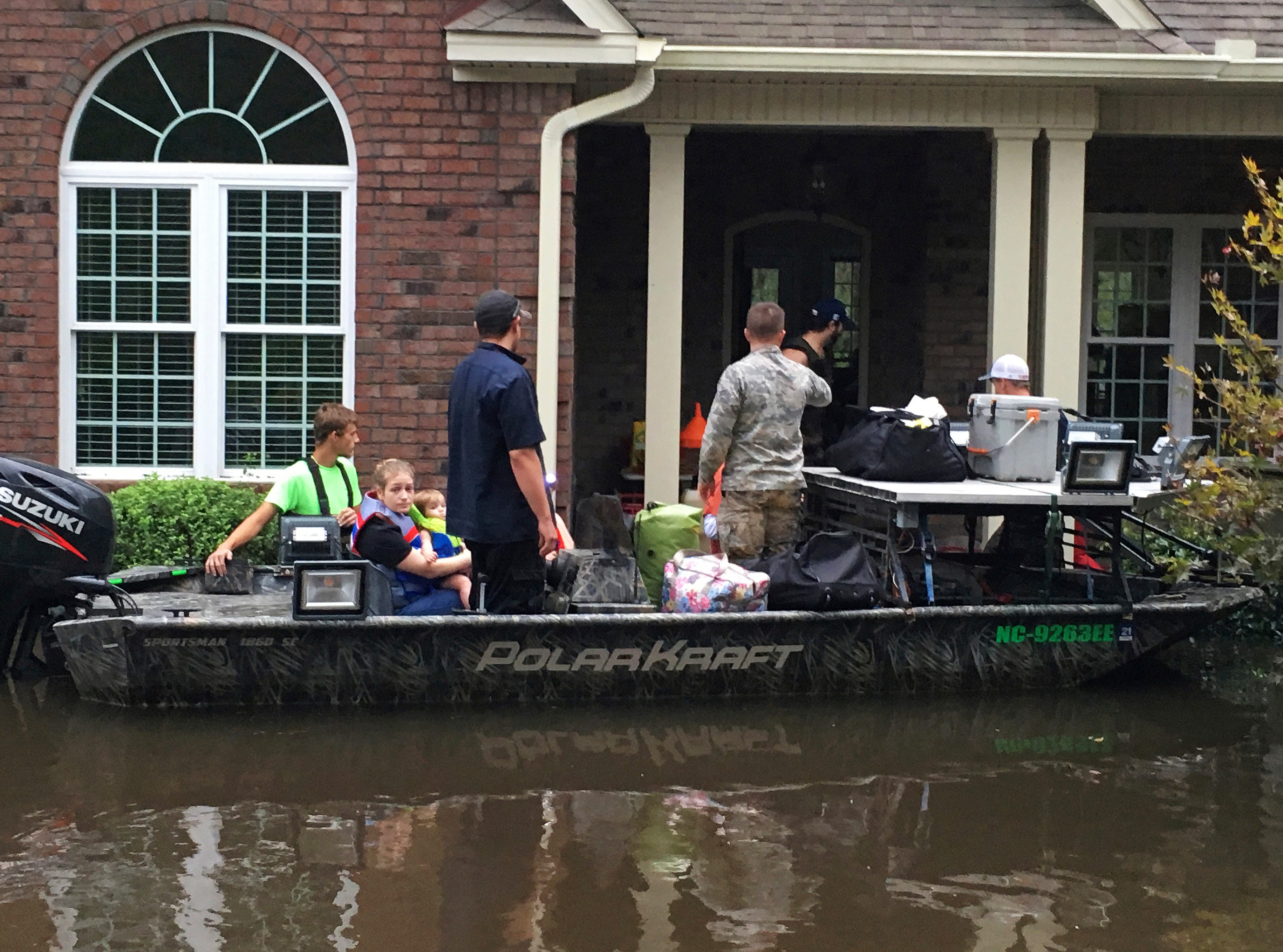 Authorities evacuate a family from rising waters caused by Florence, now a tropical storm, on Saturday, Sept. 15, 2018 in New Bern, N.C.