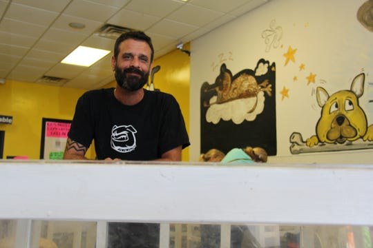 Steven Glatz, owner of Puppy Zone, poses for a photo inside his store as protesters gather outside Sept. 15.
