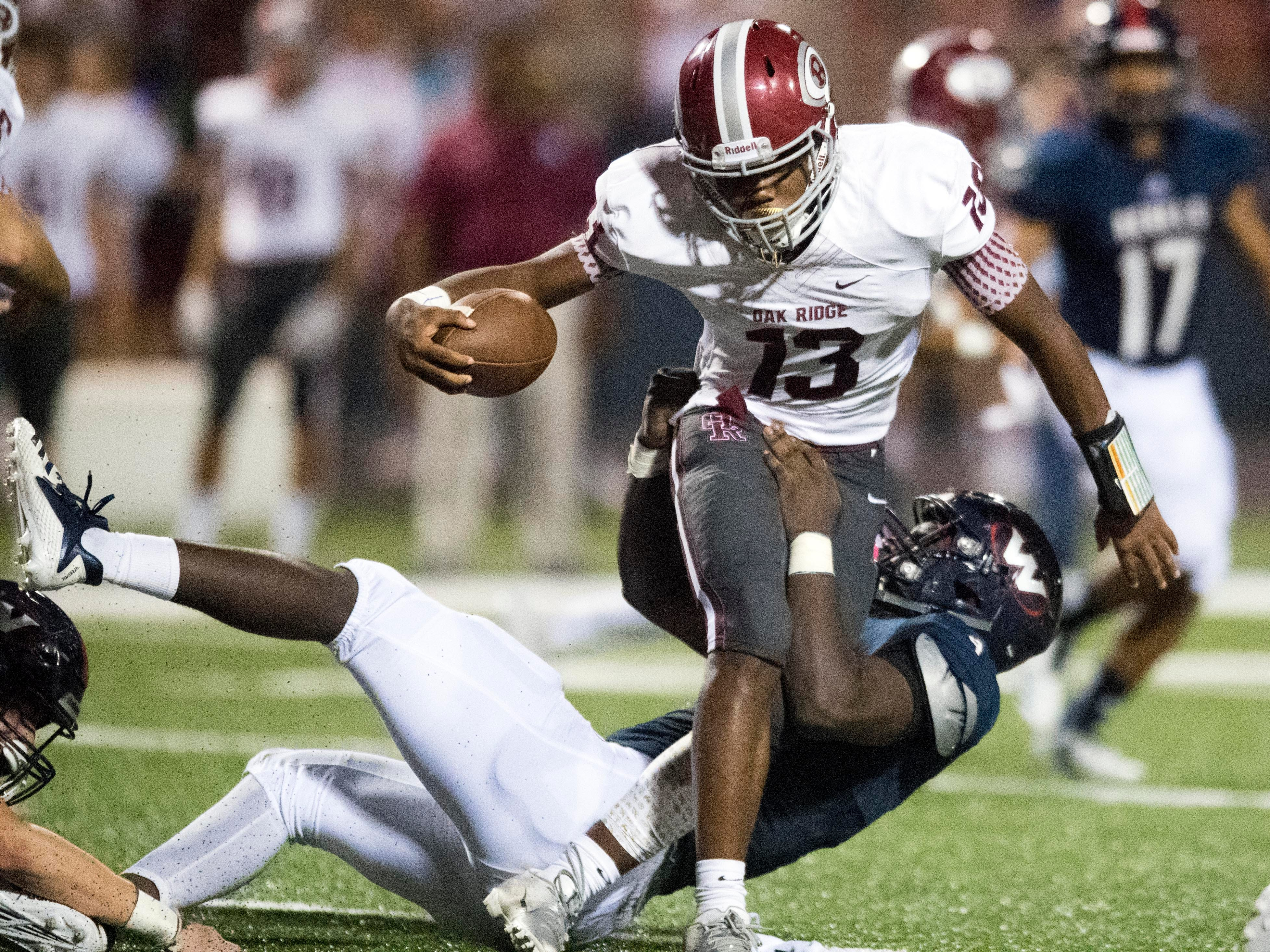 Oak Ridge's Herbert Booker (13) is pulled down by West's Tyrece Edwards (4) in the football game at West on Friday, September 14, 2018.