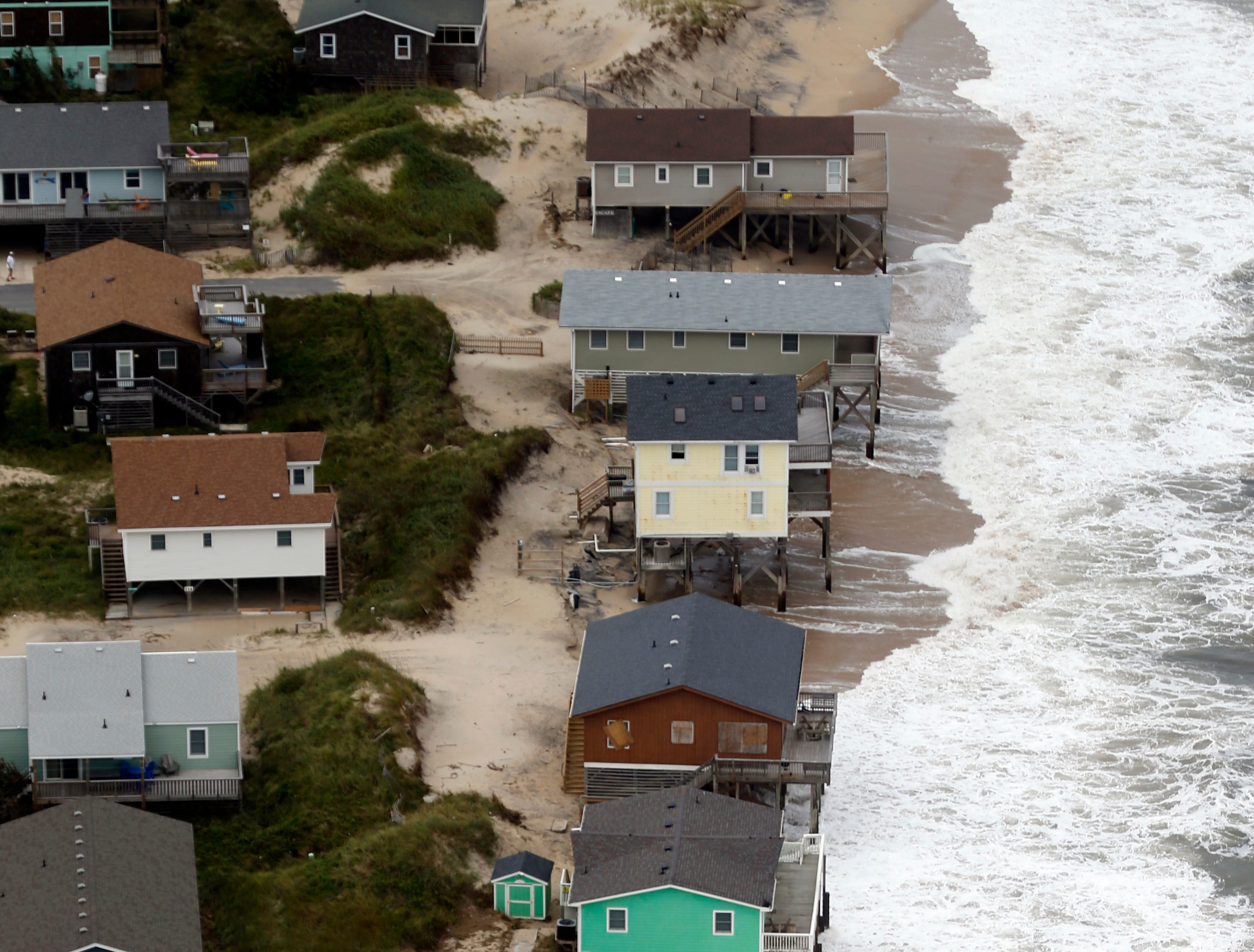 Oceanfront homes sit over rough surf from tropical storm Florence in Nags Head NC., Saturday, Sept. 15, 2018.