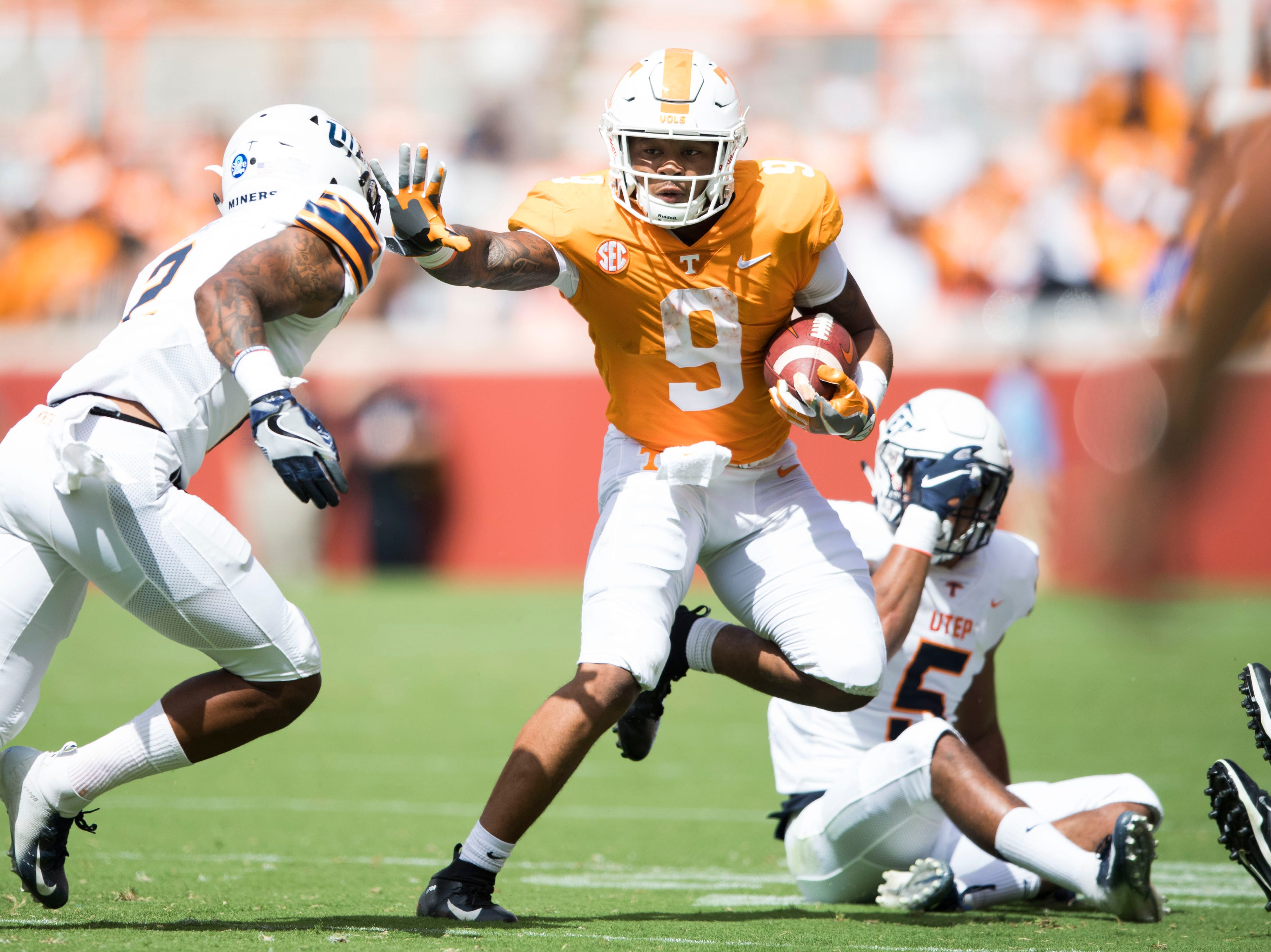 Tennessee running back Tim Jordan (9) fends off a UTEP player during a game between UT and UTEP in Neyland Stadium Sept. 15, 2018.