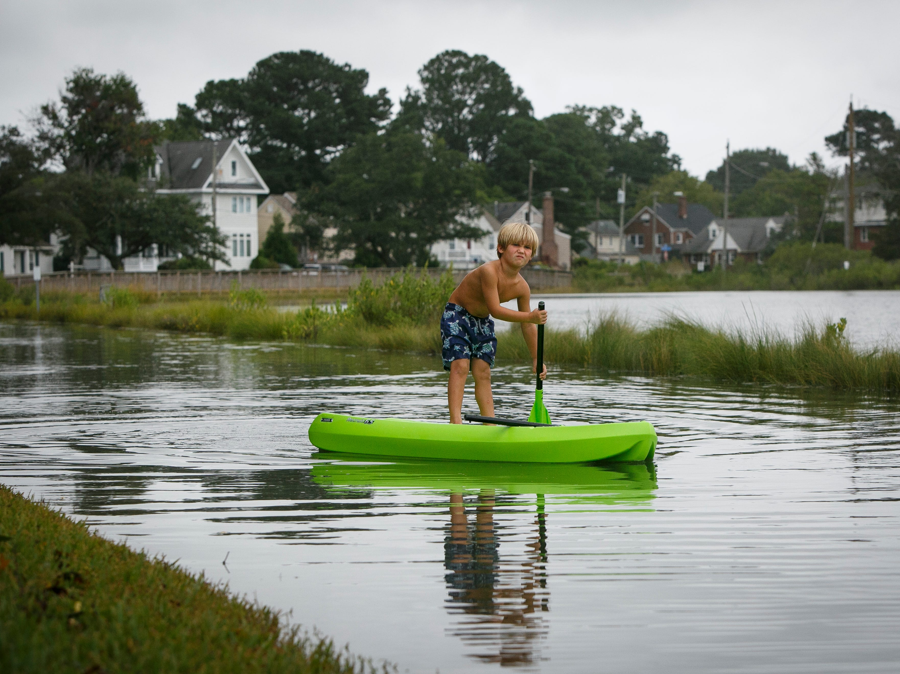 Carter Challoner, 5, paddles through flooding during high tide near Myrtle Park in the Larchmont neighborhood in Norfolk, Va., Friday, Sept.  14, 2018.