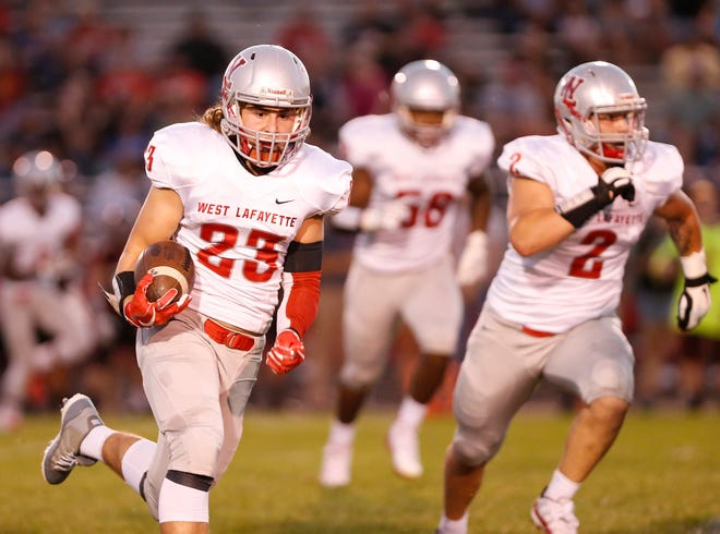 Justin Vasili of West Lafayette, right, returns an interception for a touchdown at 9:22 in the first quarter against Rensselaer Friday, September 14, 2018, in Rensselaer. West Lafayette defeated Rensselaer 69-14.