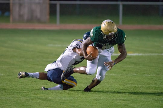 Carencro's Cody Alfred (21) tackles Acadiana High's Keontae Williams (8) as the Acadiana Wreckin' Rams take on the Carencro Bears at Acadiana High School Friday Sept. 14, 2018.