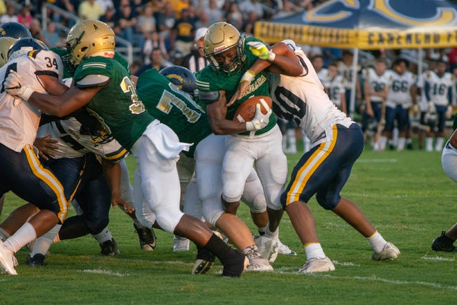 Acadiana's Dillan Monette breaks through the defense on his way to a touchdown run during the Rams' 20-13 win over Carencro on Friday at Bill Dotson Stadium.