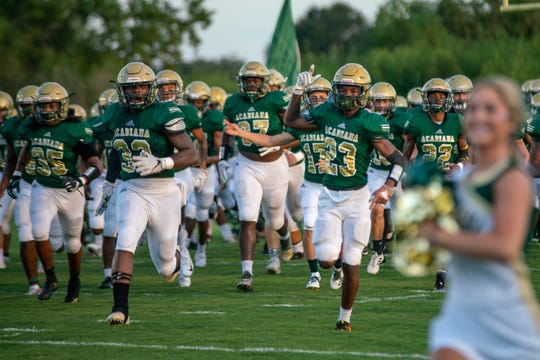 The Acadiana High Wreckin' Rams run onto the field before the game as they take on the Carencro Bears at Acadiana High School Friday, Sept. 14, 2018.