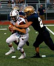 Newark quarterback Jake Sherman is sacked by Lancaster's Reese Burwell Friday night, Sept. 14, 2018, at Fulton Field in Lancaster. The Golden Gales defeated the Wildcats 62-0.