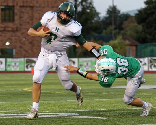 Howell quarterback Matt Hornyak (7) stiff-arms Novi's Matthew Wright on Friday, Sept. 14, 2018.