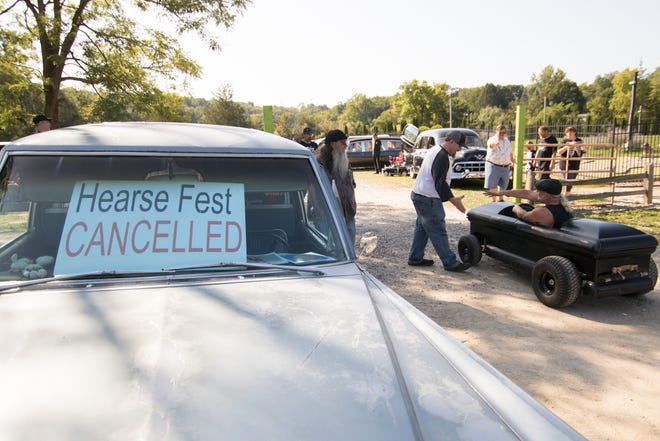 Volunteer Andy Mosier shakes hands with Dave Owens of Warren, pulling into the cancelled Hearse Fest in Hell. About 65 hearses showed up for a wedding despite the annual festival being cancelled over a disagreement with township officials.