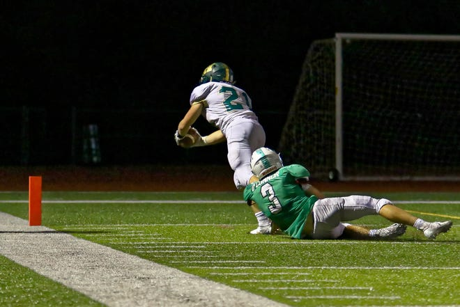 Howell's Nathan Eades (21) dives for the pylon while being hauled down by Novi's Drew O'Connor to score the winning touchdown on Friday, Sept. 14, 2018.