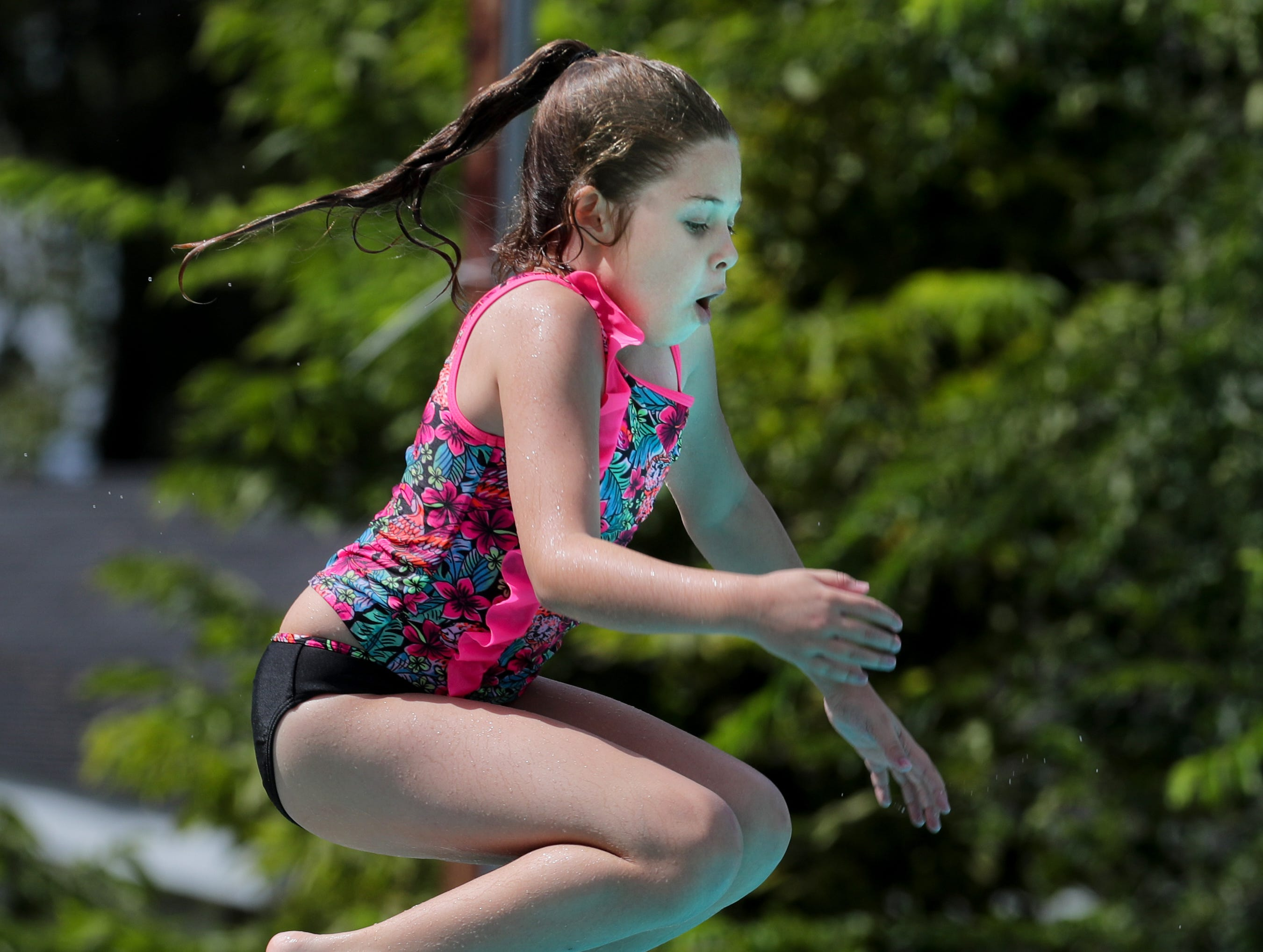 Eden Razor jumps off the diving board at the pool party during the Kentucky Kick Down Festival.  