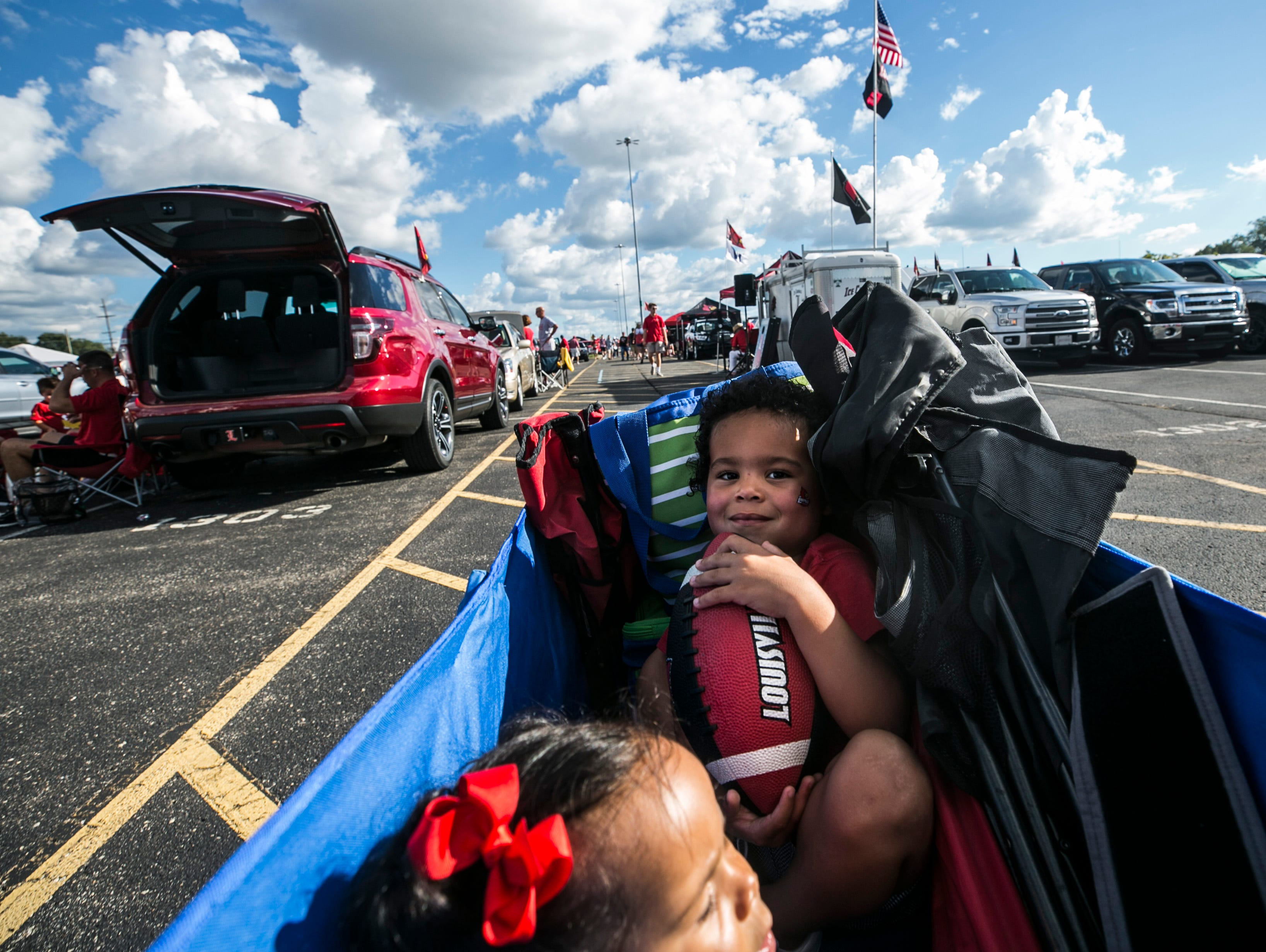 Bo Burfict, 3, holds a football as he and sister Landon get a wagon ride towards Cardinal Stadium before the Louisville's game against Western Kentucky Saturday, Sept. 15, 2018.
