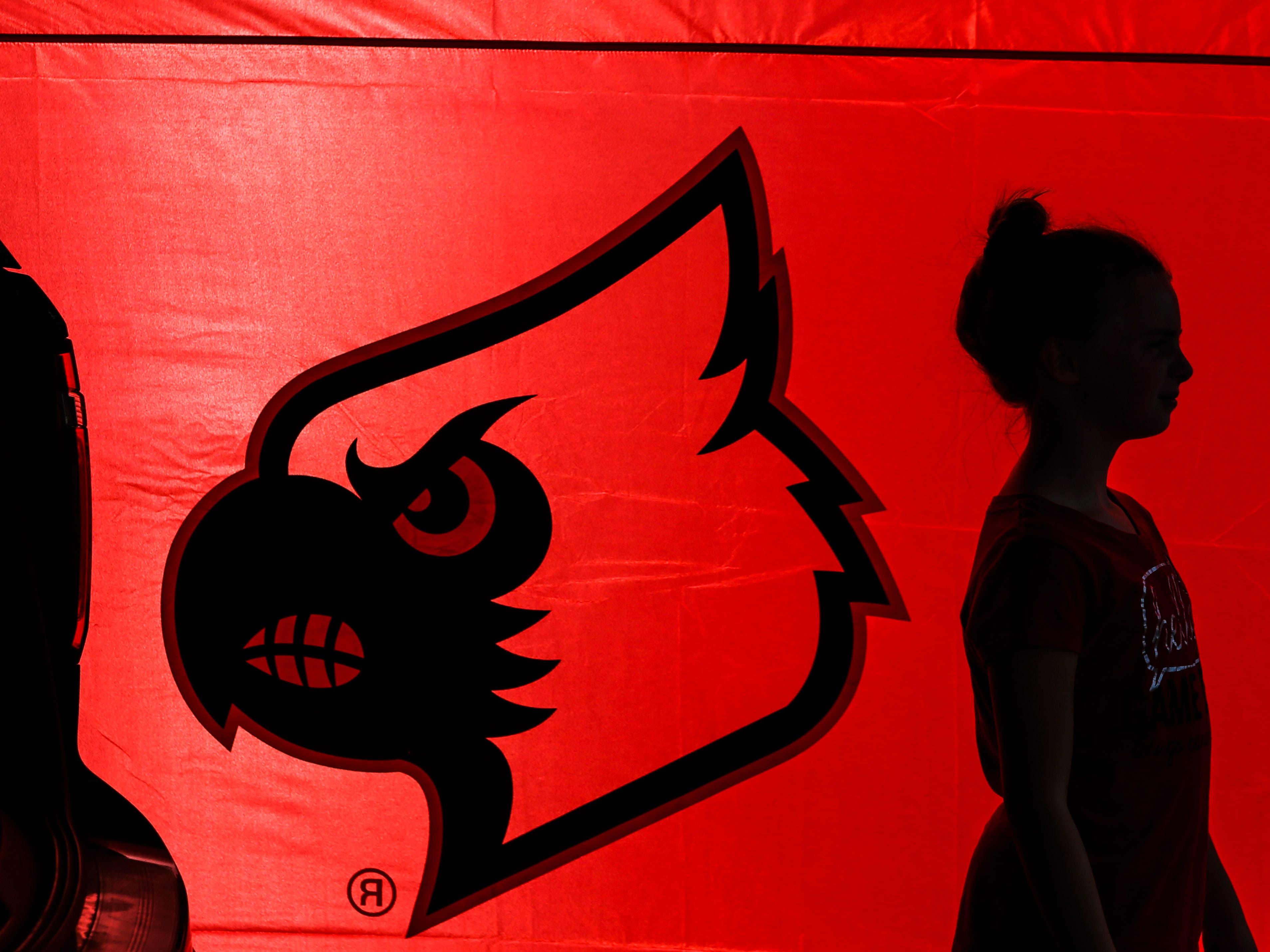Kaleigh Kaufman, 10, stands in her family's tailgate tent as she waits before the Louisville-Western Kentucky football game Saturday, Sept. 15, 2018.