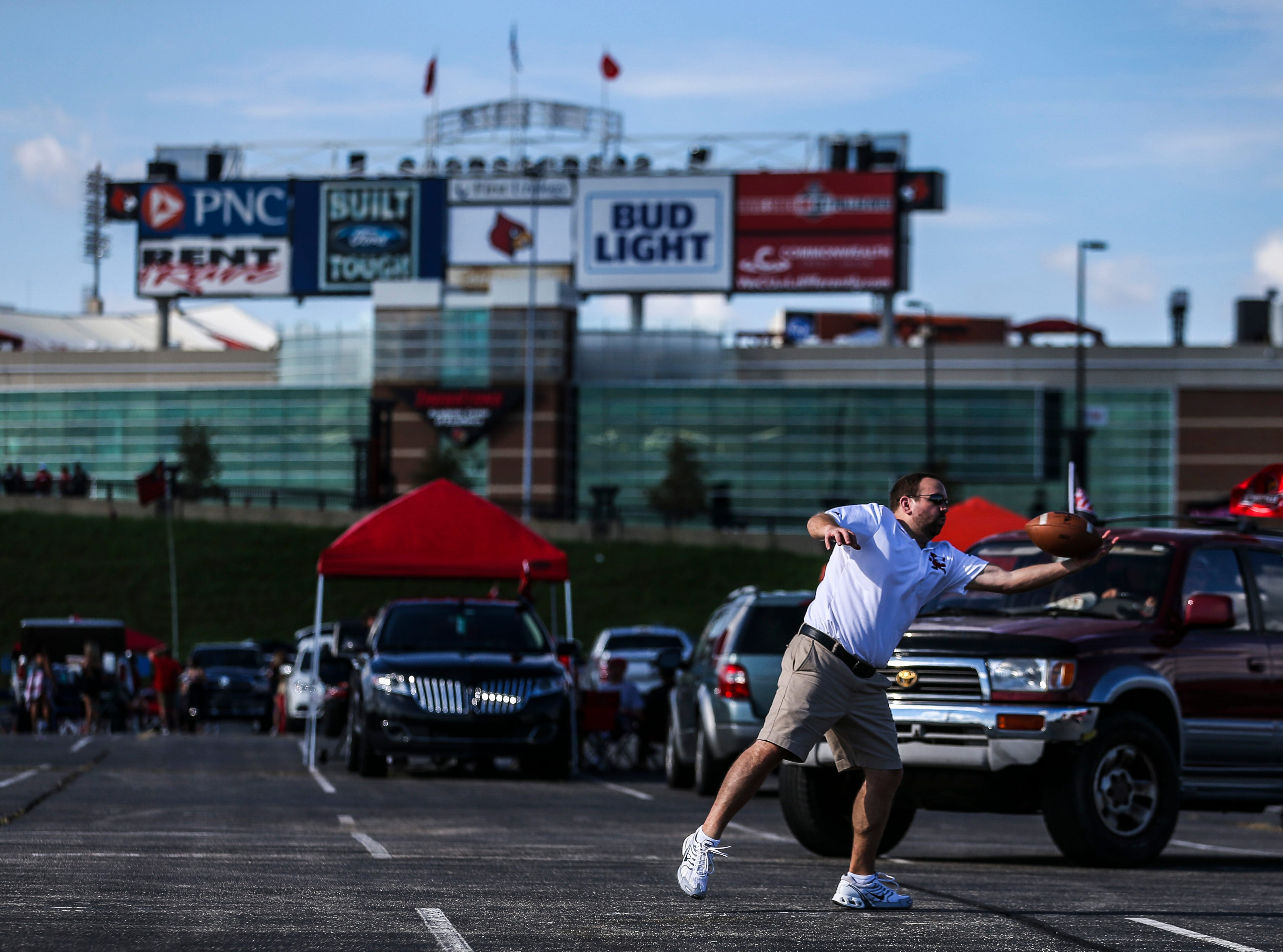 A Louisville fan tries to make a catch while throwing the ball around in a parking lot before the Cardinals' game against Western Kentucky Saturday, Sept. 15, 2018.
