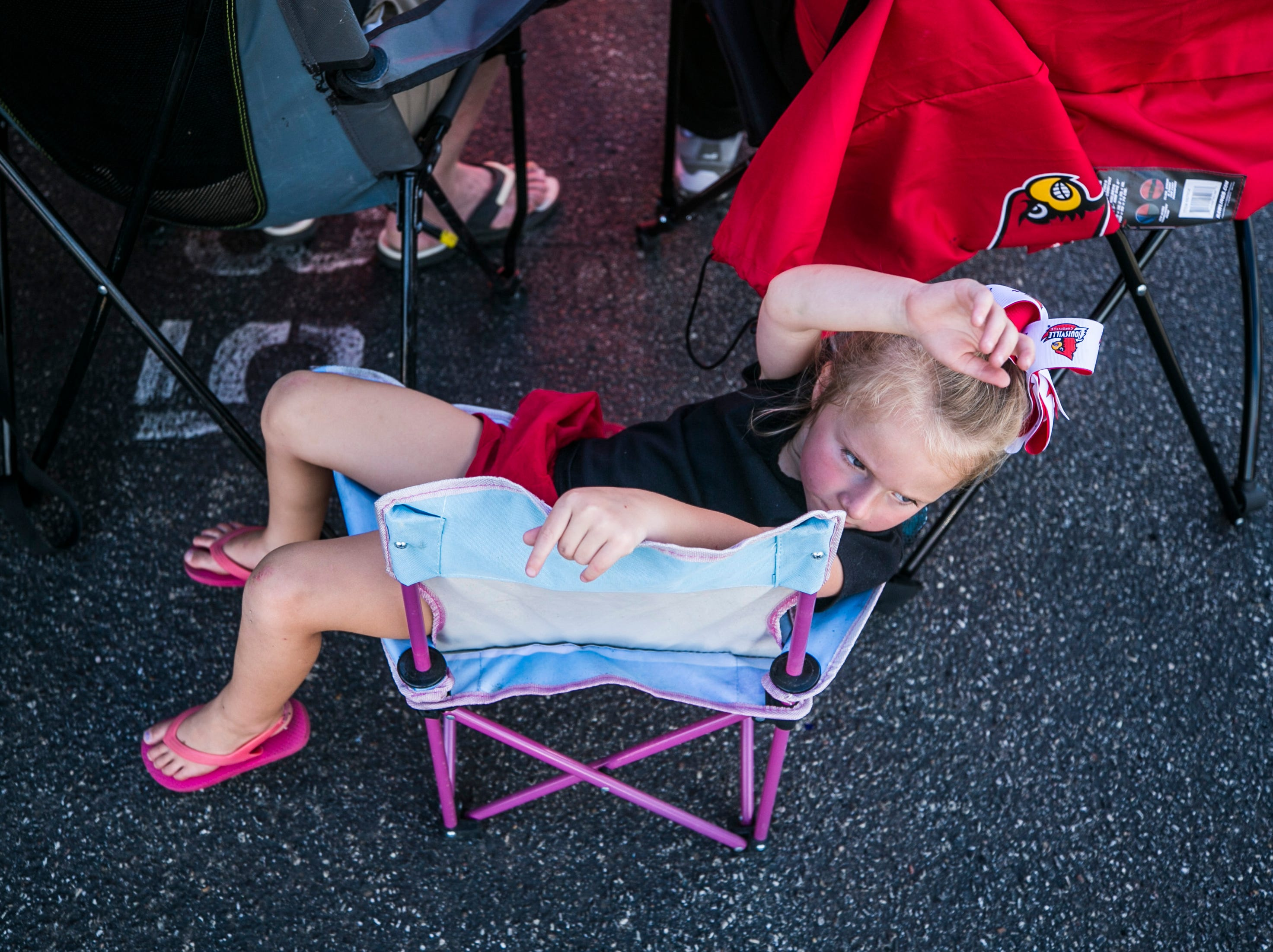 Avery Kaufman, 4, relaxes in her folding chair while tailgating before the Cardinals' game against Western Kentucky Saturday, Sept. 15, 2018.