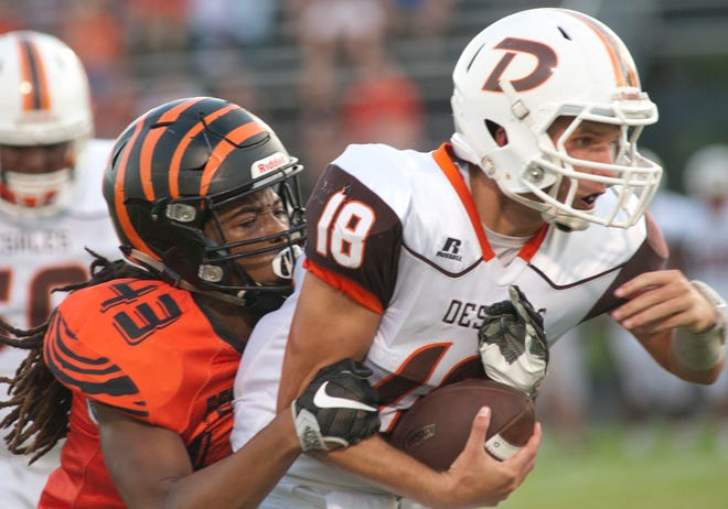 Fern Creek defensive lineman Cidney Mills wraps up DeSales quarterback Aaron Pfaadt during the Fern Creek vs. DeSales football game at Fern Creek.September 14, 2018
