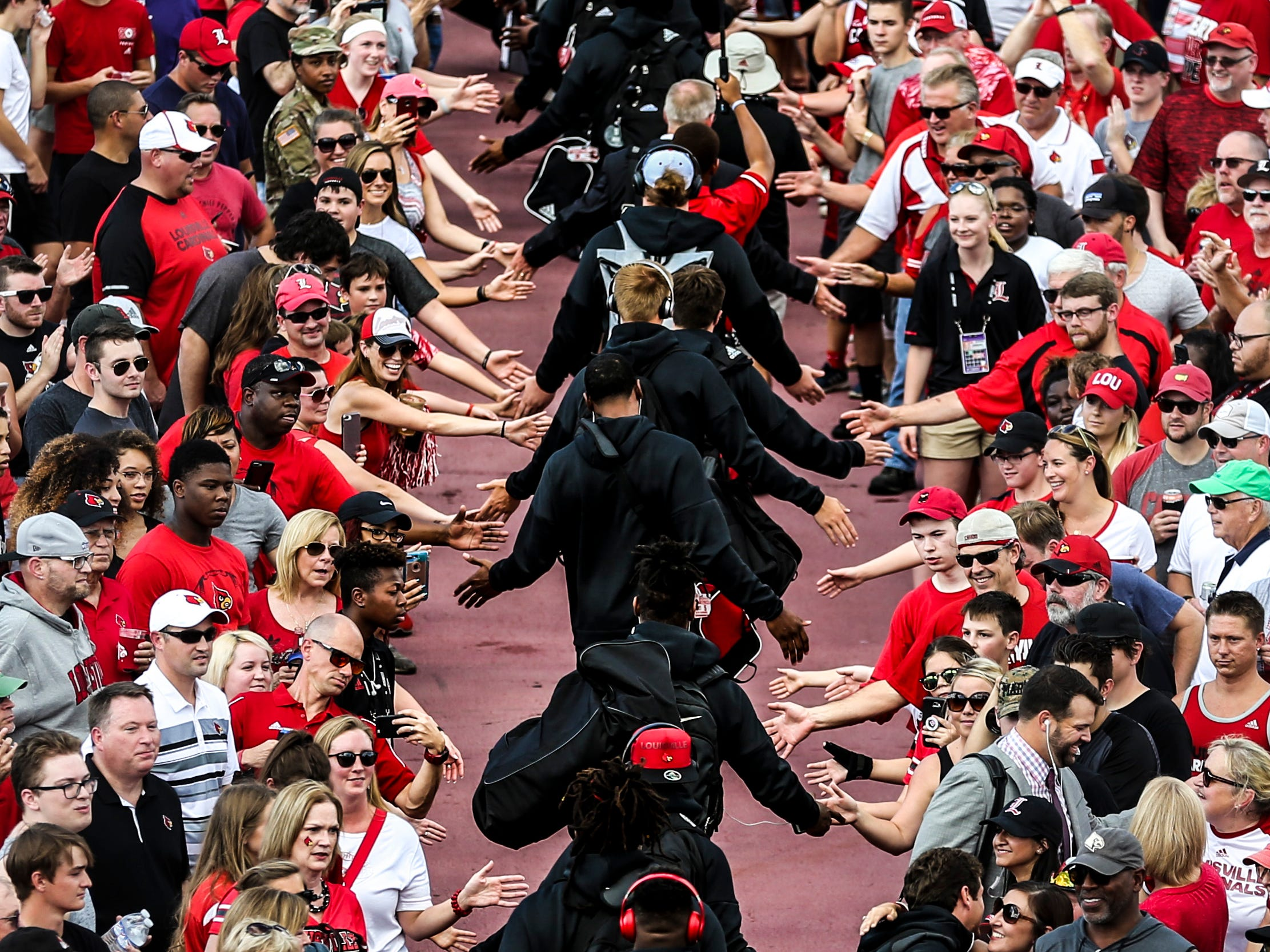 The Louisville football team greets fans as they walk towards Cardinal Stadium before the game against Western Kentucky Saturday, Sept. 15, 2018.