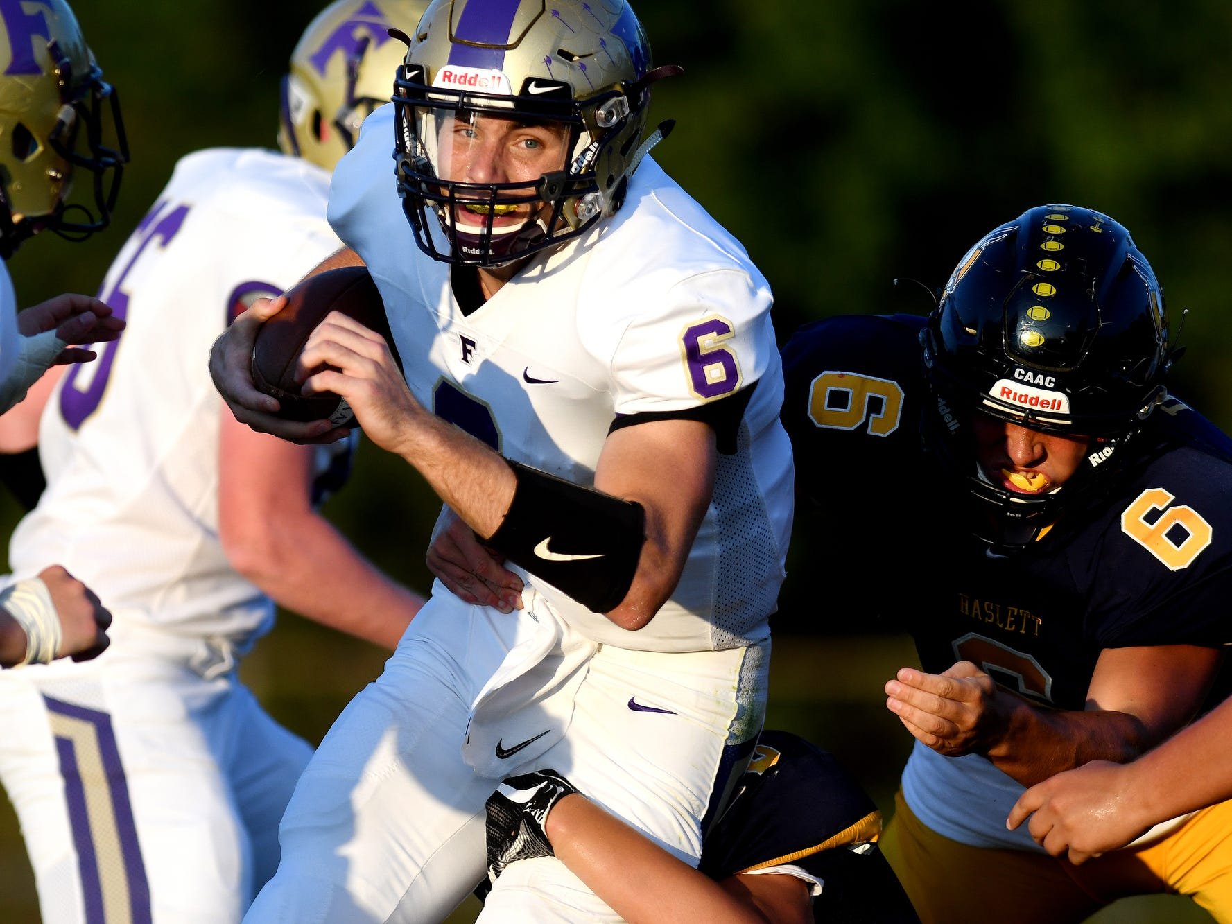 Fowlerville's quarterback Geoffrey Knaggs, left, is tackled by Haslett defenders at the end of a run during the first quarter on Friday, Sept. 14, 2018, at Haslett High School.