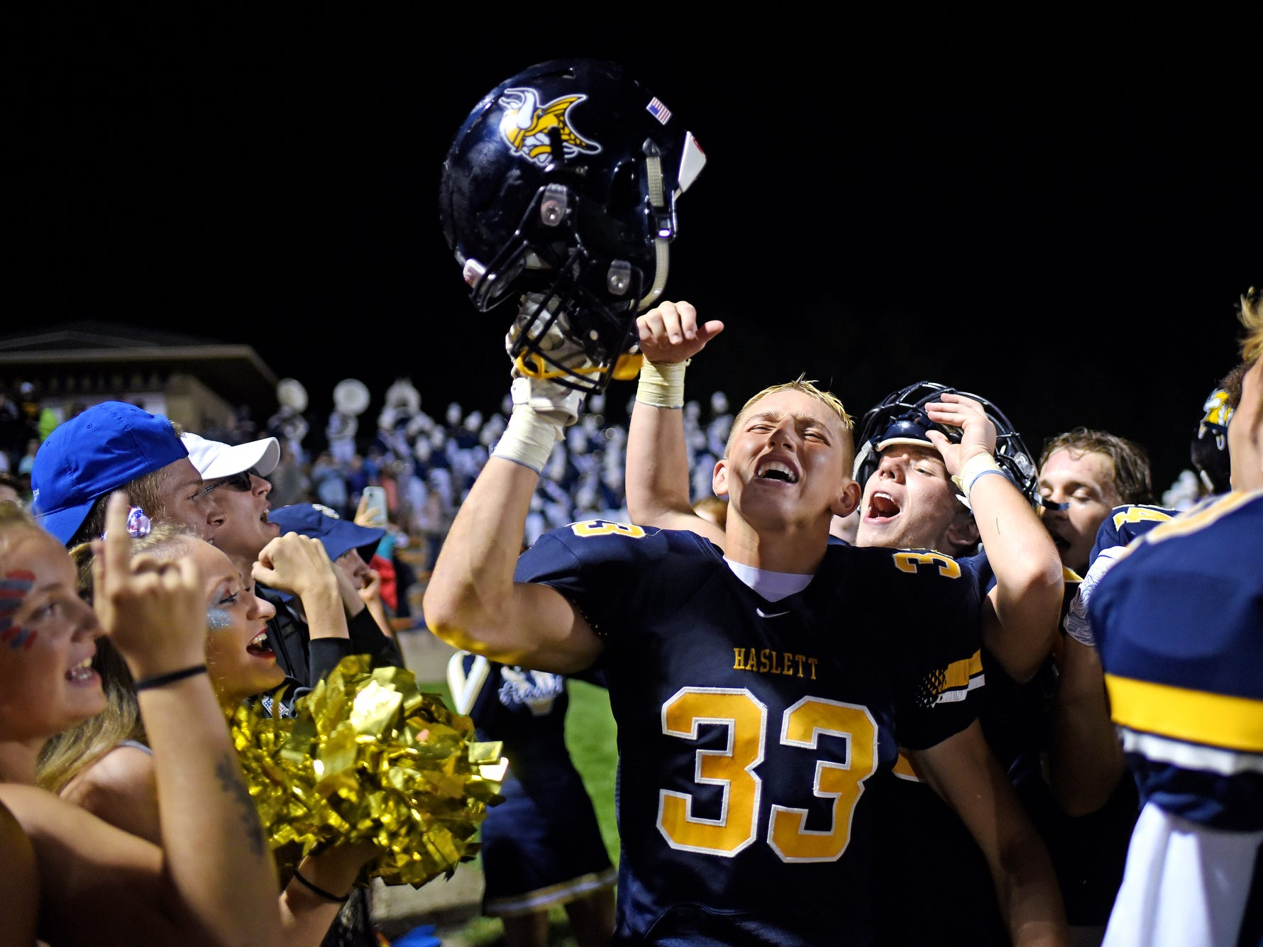 Haslett's Quentin Hernandez, center, celebrates the Vikings victory with teammates and fans after the game on Friday, Sept. 14, 2018, at Haslett High School.