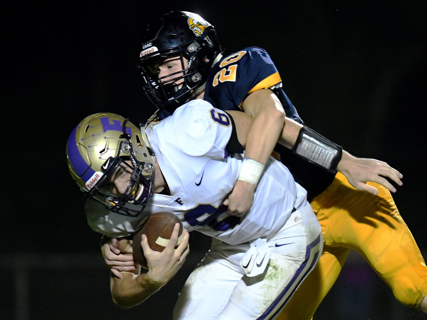 Haslett's Caleb Beebe, right, sacks Fowlerville quarterback Geoffrey Knaggs during the fourth quarter on Friday, Sept. 14, 2018, at Haslett High School.