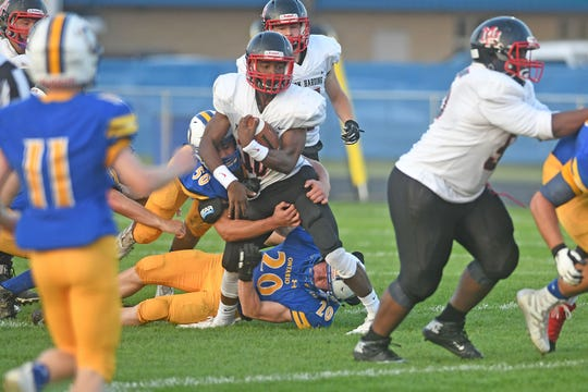 Marion Harding's DeAndre Ayers tries to break a tackle as Ontario defenders Mitch Pittman and Noah Creed try to bring him down.