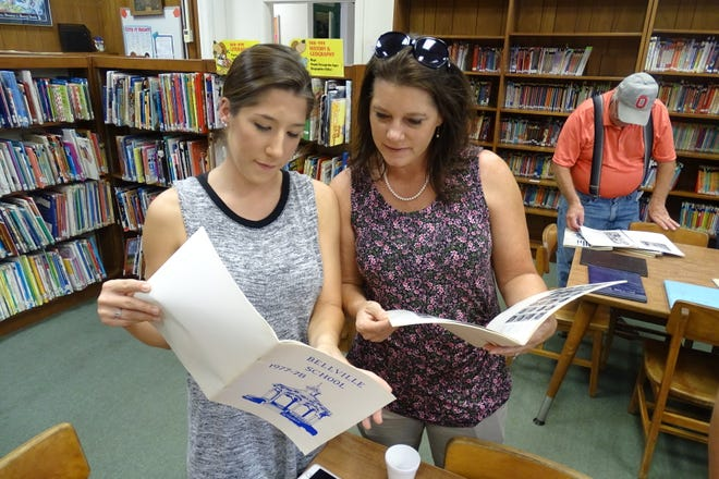Susie Beveridge, left, and her mother, DeAnn Smith, look over old year books Saturday at the Bellville Elementary School.