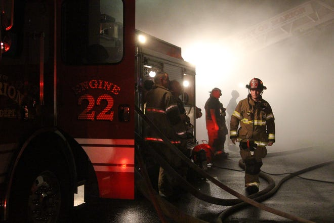 Marion firefighters battle a house fire on East Mark Street early Saturday morning.