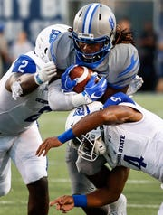 Memphis running back Darrell Henderson (middle) runs over Georgia State defenders Ed Curney (left) and Khai Anderson (right) during Friday's game.