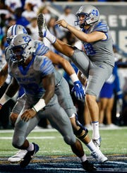 University of Memphis punter Adam Williams (right) kicks a ball against Georgia State University during action in Memphis, Tenn., Friday, September 14, 2018.