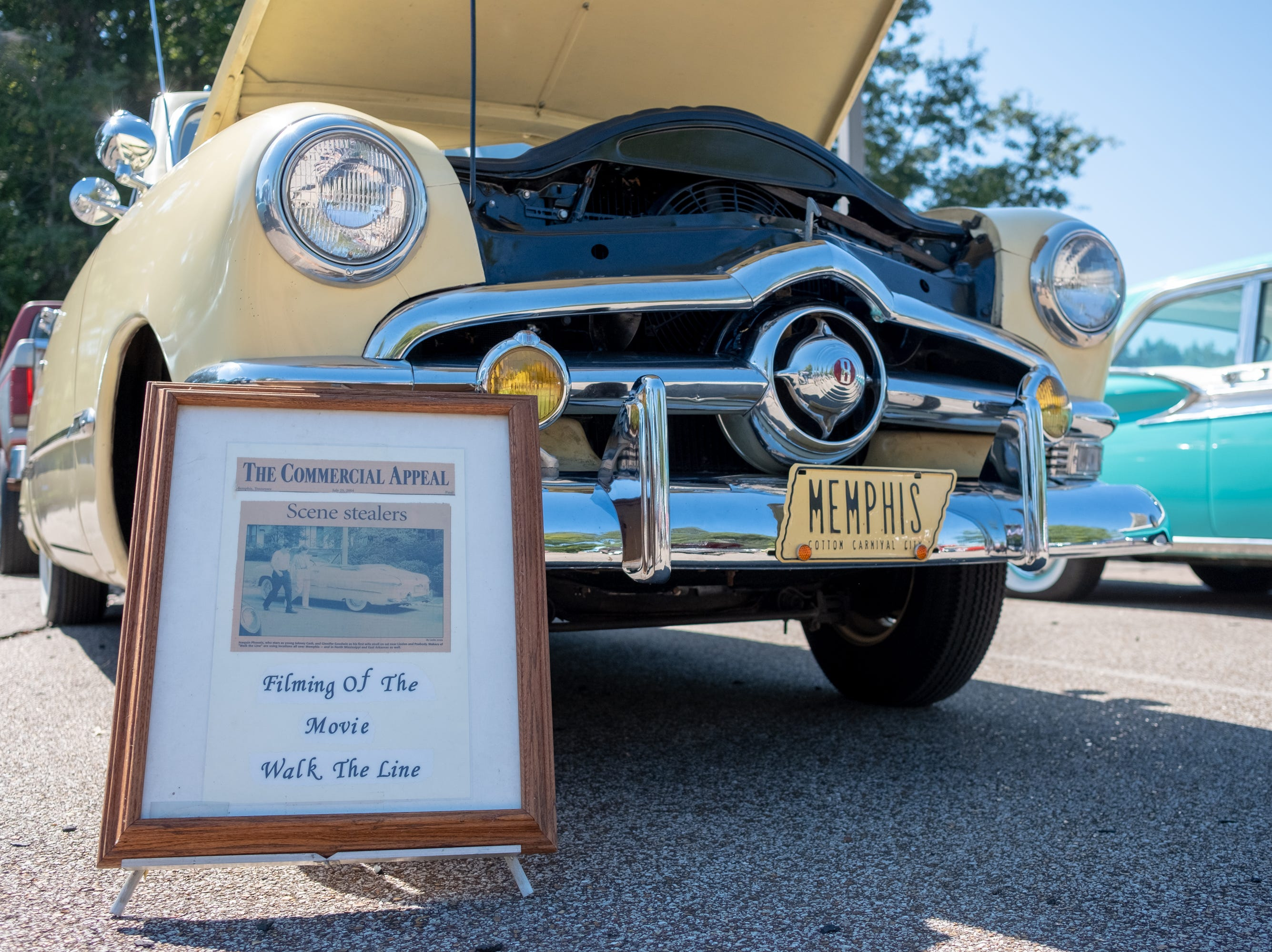 "A car that was featured in the movie ""Walk the Line"" sits next to a sign displaying a photograph from the Commercial Appeal at the Collierville Classic Car Show on Sept. 15, 2018."