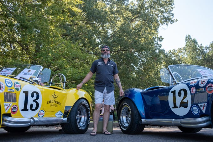 Brett Call poses with his pair of Ford Cobras — the yellow is from 1965 and the blue is from 1966 —  at the Collierville Classic Car show on Sept. 15, 2018.