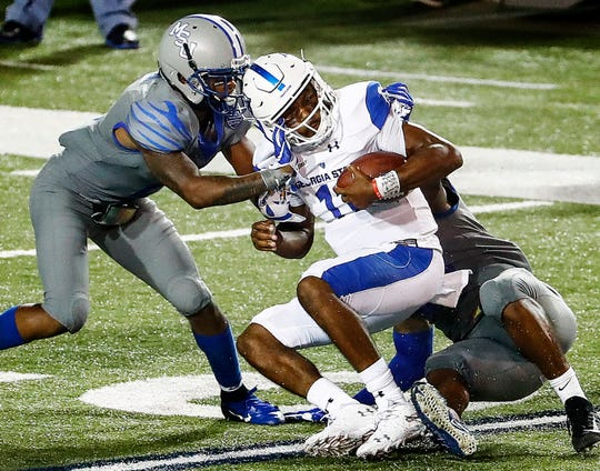 Georgia State University quarterback Aaron Winchester (middle) is brought down by the University of Memphis defense during action in Memphis, Tenn., Friday, September 14, 2018.