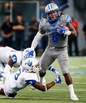 University of Memphis running back Darrell Henderson (right) runs over the Georgia State University defender Chris Bacon (left) during action in Memphis, Tenn., Friday, September 14, 2018.