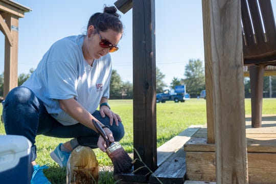 Landis DeRossitte coats wood with new stain at the Epiphany Community Garden in Collierville on Saturday, Sept. 15, 2018.