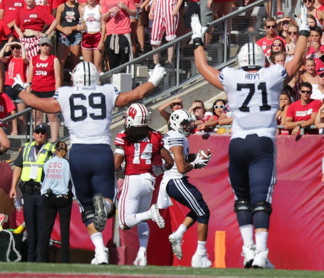 BYU players celebrate a touchdown by quarterback Stacy Conner against Wisconsin on Saturday.