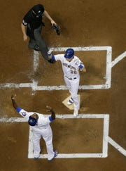 Christian Yelich is congratulated at home by Lorenzo Cain after hitting a two-run home run
