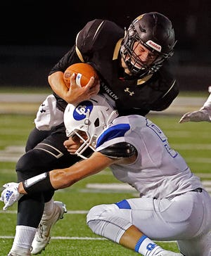 Franklin's quarterback Matt Designer  is hit hard by Oak Creek's Colin Kalinowski.
