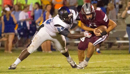 Alabama Christian's Reece Solar is grabbed by Montgomery Catholic's CJ Person for a tackle.
