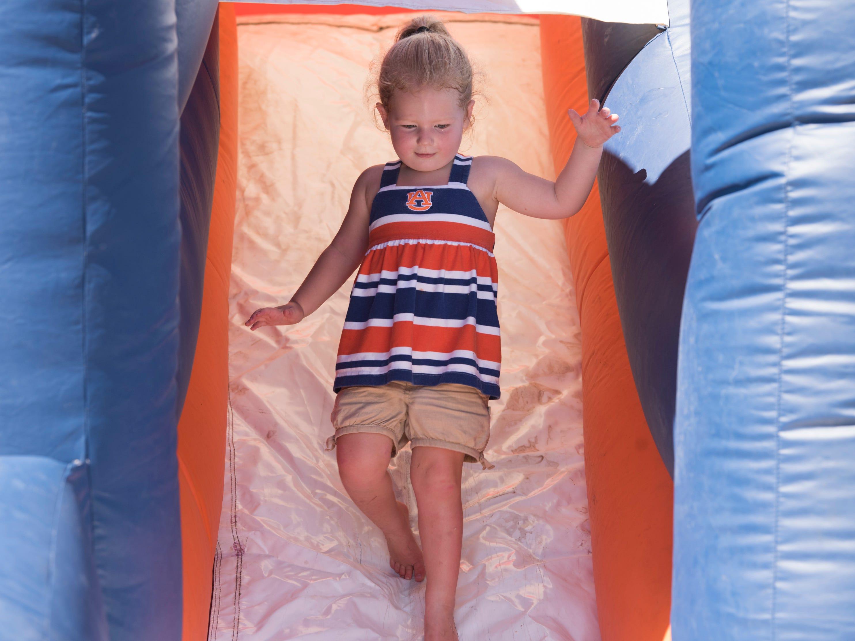 Corinne Pittman, 3, goes down a bouncy slide outside Jordan-Hare Stadium in Auburn, Ala., on Saturday, Sept. 15, 2018.
