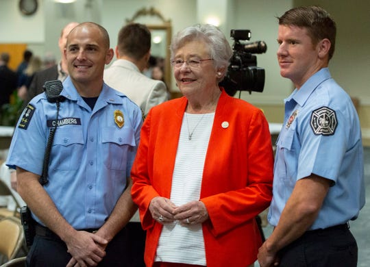 Gov. Kay Ivey poses for a photo with two Montgomery firefighters during a brunch at Frazer United Methodist Church.