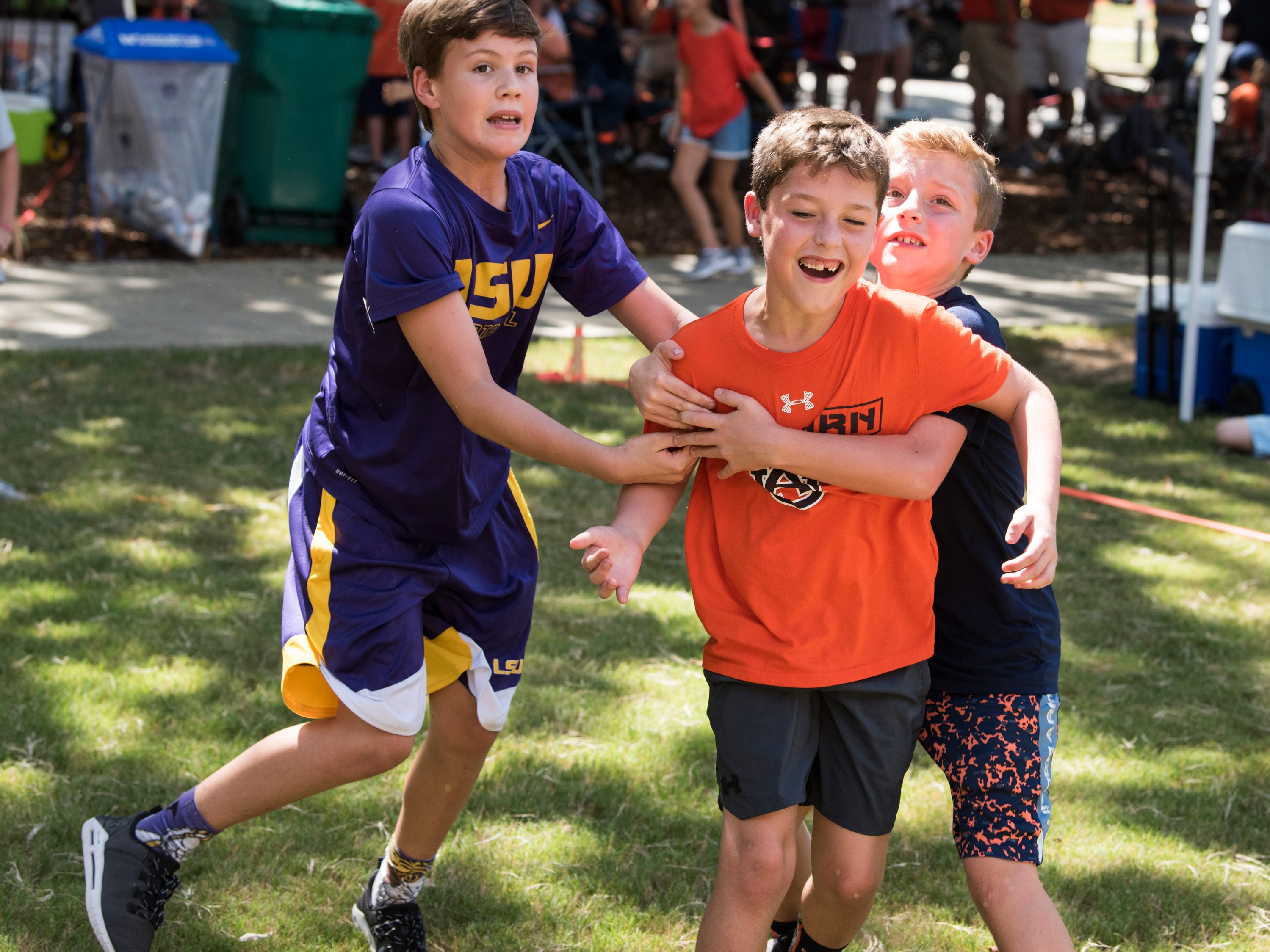 Patrick McQueen, 11, from left, Kody and Kale Barganier, both 9, play some tailgate football outside Jordan-Hare Stadium in Auburn, Ala., on Saturday, Sept. 15, 2018.