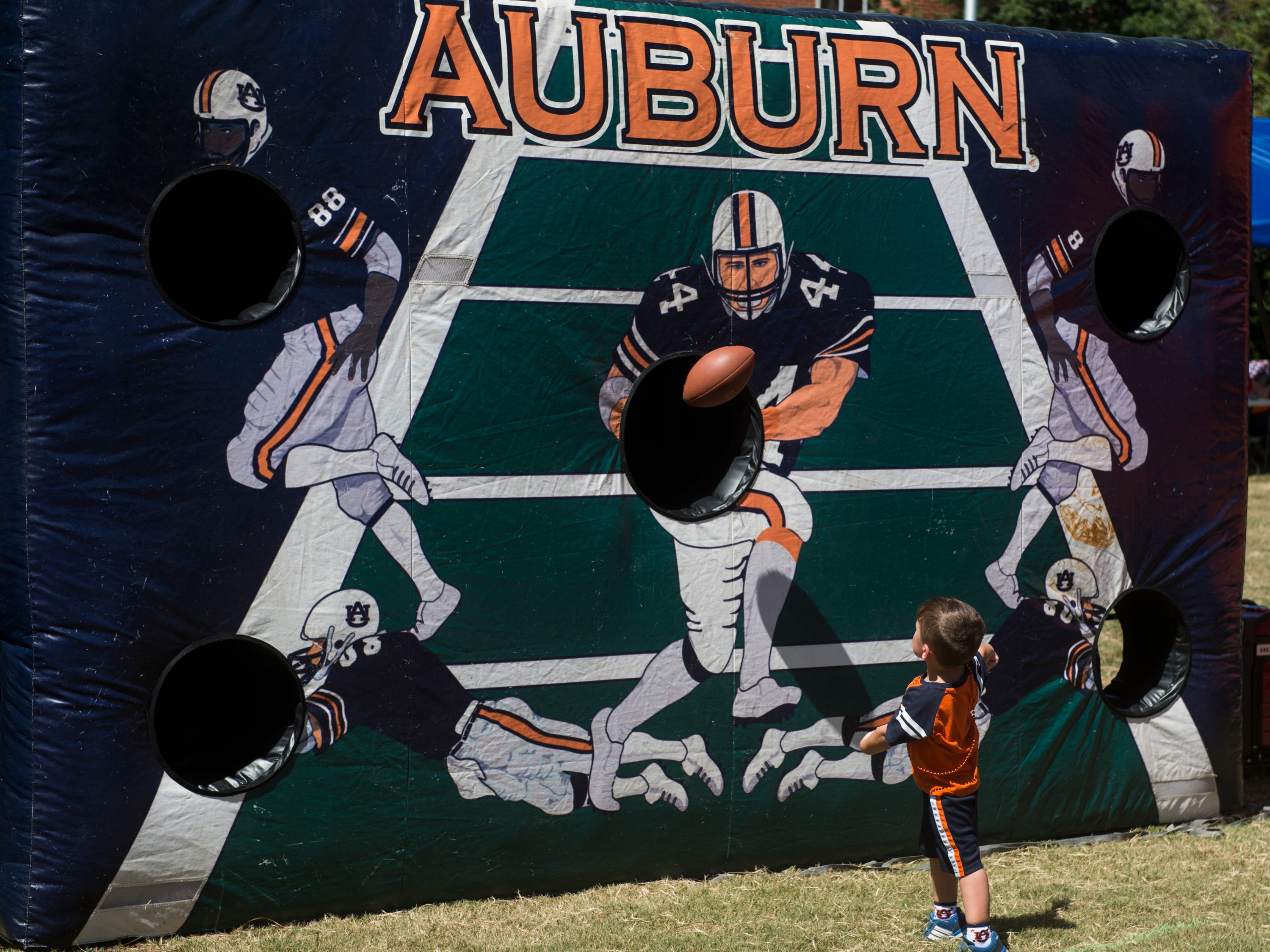 Asher Stevenson, 3, plays a game at a tailgate outside Jordan-Hare Stadium in Auburn, Ala., on Saturday, Sept. 15, 2018.