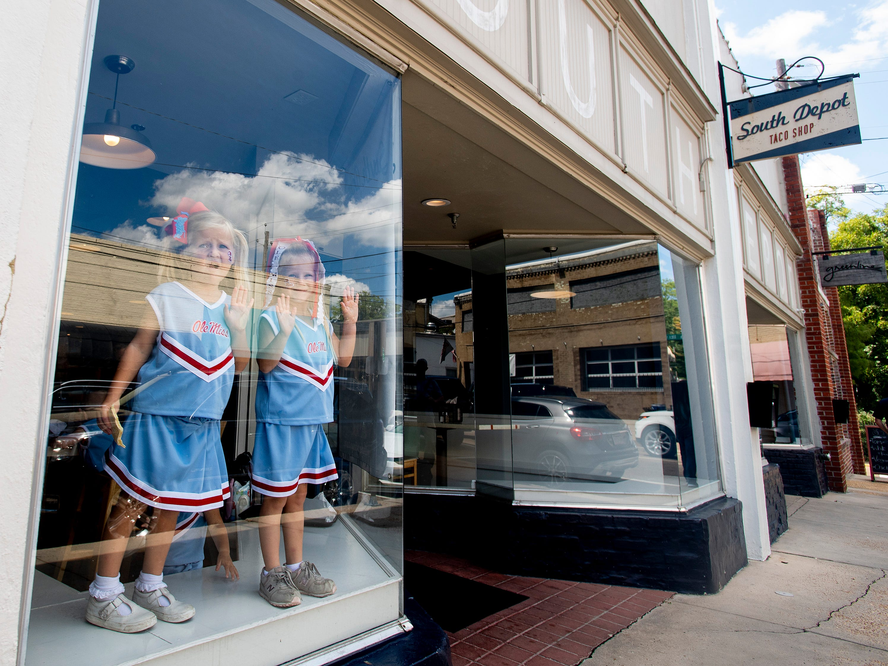 Young Ole Miss fans dressed as cheerleaders stand in a restaurant window in Oxford, Ms., on Saturday September 15, 2018.
