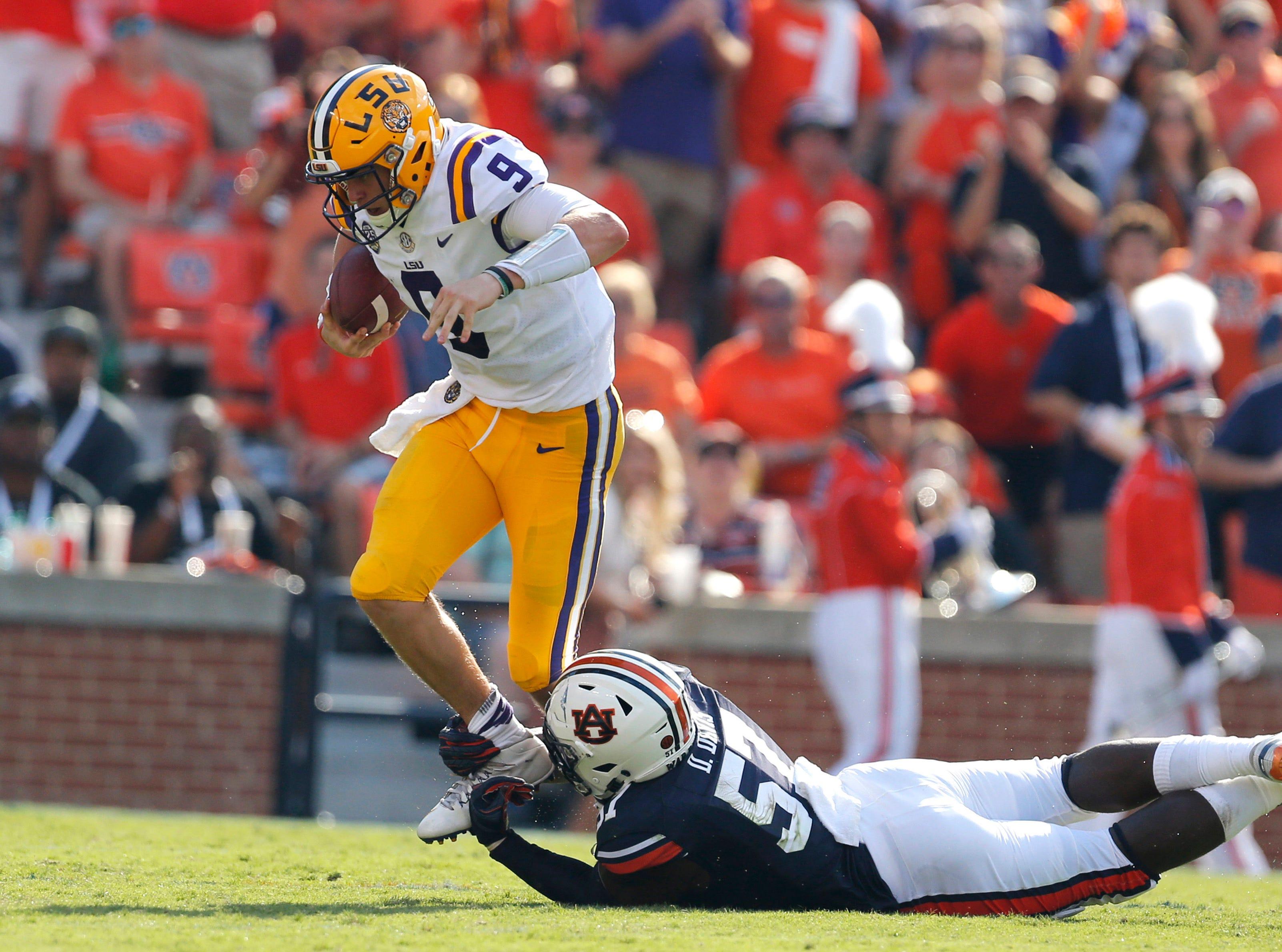 Sep 15, 2018; Auburn, AL, USA; LSU Tigers quarterback Joe Burrow (9) is tripped by Auburn Tigers linebacker Seshaun Davis (57) during the second quarter at Jordan-Hare Stadium. Mandatory Credit: John Reed-USA TODAY Sports