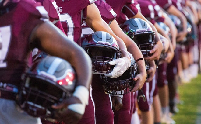 Alabama Christian football players tuck their helmets under their arms during the National Anthem.