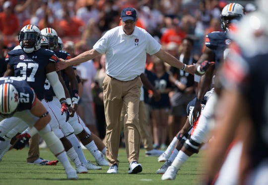 Auburn head coach Gus Malzahn acknowledges each player as they warm up before Auburn takes on LSU at Jordan-Hare Stadium in Auburn, Ala., on Saturday, Sept. 15, 2018.